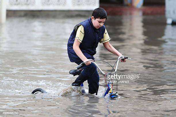 A boy rides a bicycle in a flooded street in the Qatari capital Doha following heavy rainfall on November 25 2015 Qatar was hit by heavy flooding...