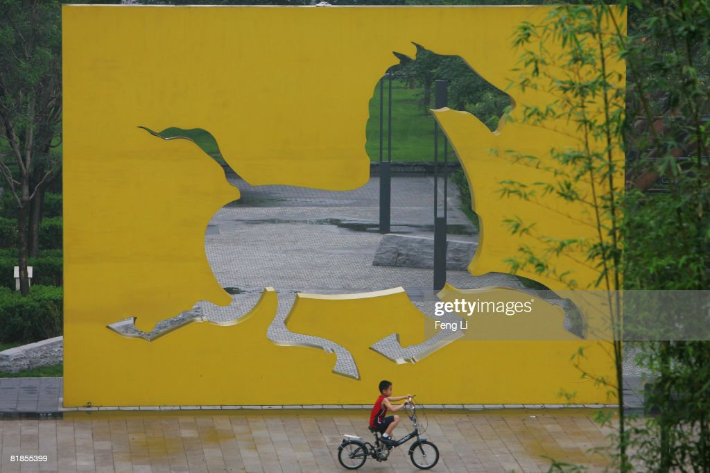 A boy rides a bicycle past an horse shaped sculpture on July 8, 2008 in Beijing, China. Beijing will host the 2008 Olympics from August 8 to 24, 2008.