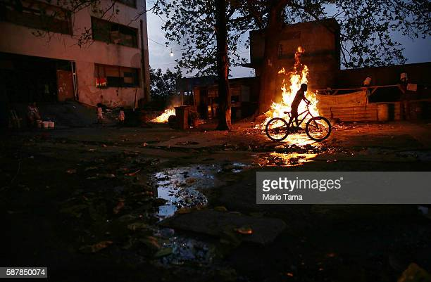 A boy rides a bike past a trash fire outside an occupied building in the Mangueira 'favela' community on August 9 2016 in Rio de Janeiro Brazil...