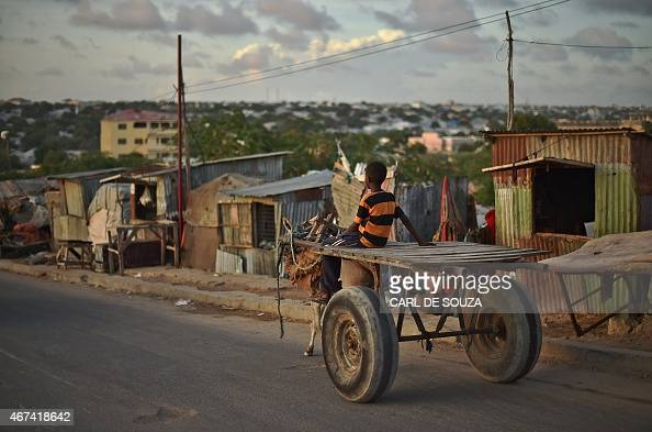 A boy rides a donkey cart past an internally displaced persons camp near the Somali Parliament in Mogadishu on March 24 2015 AFP PHOTO/Carl de Souza