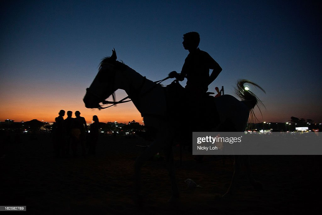 A boy rides a horse during sunset at the Marina Beach on February 24, 2013 in Chennai, India. Marina Beach is an urban beach along the Bay of Bengal, which is part of the Indian Ocean. The beach runs a distance of 13km (8.1 miles), making it the longest natural urban beach in the country and the world's second longest.
