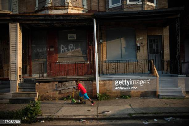 A boy rides a scooter past abandoned homes on August 20 2013 in the Whitman Park neighborhood of Camden New Jersey The town of Camden which was once...