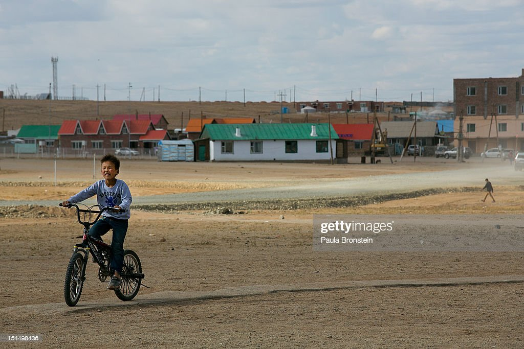 A boy rides his bicycle home October 13, 2012 in Khanbogd, Mongolia. The population of Khanbogd has doubled in the last few years along with growing business needs because Oyu Tolgoi employs hundreds who have moved there.The Oyu Tolgoi copper and gold mine (translated means Turquiose Hill) is a combined open pit and underground mining project. While the construction continues open pit mining is currently underway with full production expected later in 2012. When the mine starts full operation the country will be set to become one of the world's top copper and gold producers with estimates of 450,000 tons of copper and 330,000 ounces of gold. Financing for the project has come in part from the Rio Tinto Group and an investment agreement between Ivanhoe Mines and the government of Mongolia. Mongolia's largest foreign investment project to date which is projected to add one-third of future value to the country's GDP. Many estimate Mongolia to be the world's fastest growing economy with an estimated $1.3 trillion in untapped mineral resources.