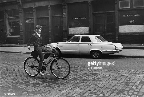 A boy rides his bicycle without using his hands on a cobbled street in Greenwich Village New York City circa 1967