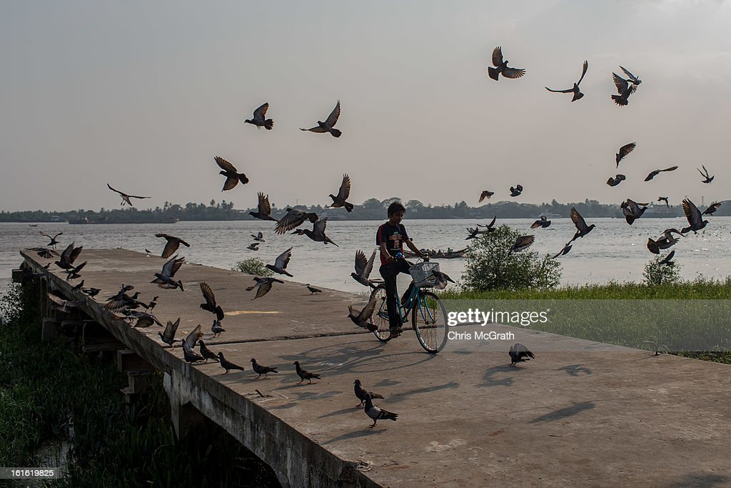 A boy rides his bike through a flock of birds at a jetty on February 13, 2013 in Yangon, Burma. Myanmar is going through rapid political and economic reforms initiated by the countries first civilian president Thein Sein after years of military junta rule.