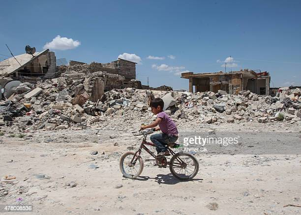 A boy rides his cycles in the streets of the destroyed Syrian town of Kobane also known as Ain alArab Syria June 20 2015 Kurdish fighters with the...