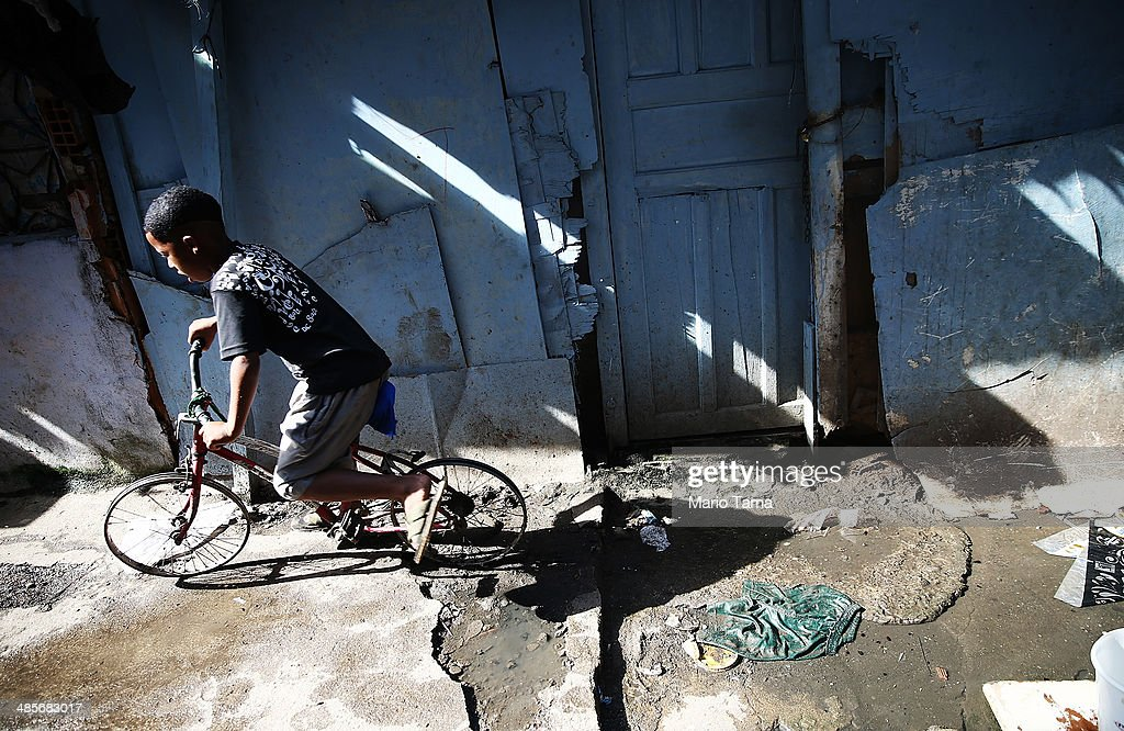 A boy rides past on a bike with no tires in an impoverished section of the occupied Complexo da Mare, one of the largest 'favela' complexes in Rio, on April 19, 2014 in Rio de Janeiro, Brazil. The Brazilian government has deployed nearly 3,000 federal troops to occupy the group of violence-plagued slums ahead of the June 12 start of the 2014 FIFA World Cup. The group of 16 communities house around 130,000 residents and had been dominated by drug gangs and militias. Mare is located close to Rio's international airport and has been mentioned as a likely pacification target for the police amid the city's efforts to improve security ahead of the 2014 FIFA World Cup and Rio 2016 Olympic Games.