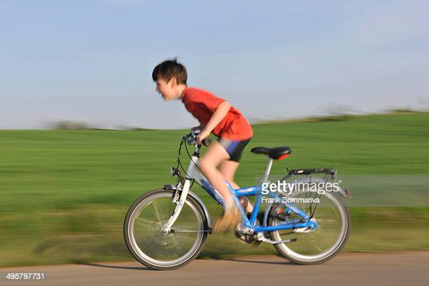 Boy riding a bicycle on a tarmaced track, Erfurt, Thuringia, Germany