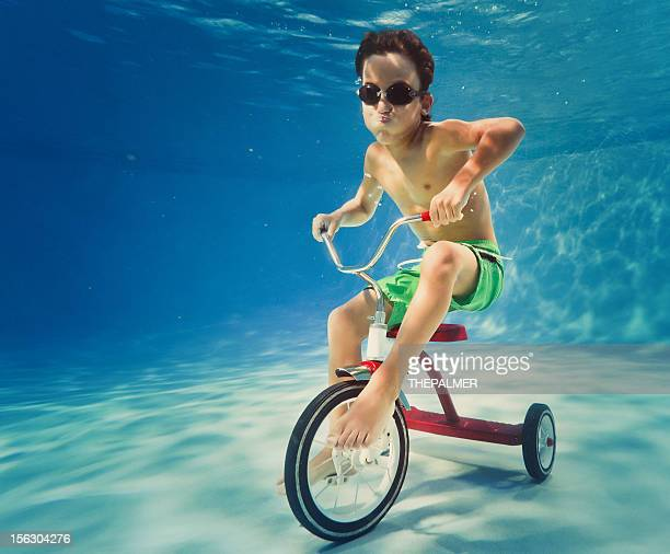 boy riding a tricycle underwater