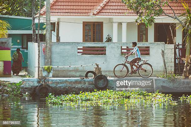 Boy riding bicycle along the Kerala Backwaters in India
