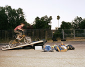 Boy (11-15) riding bicycle off jump over friends (blurred motion)