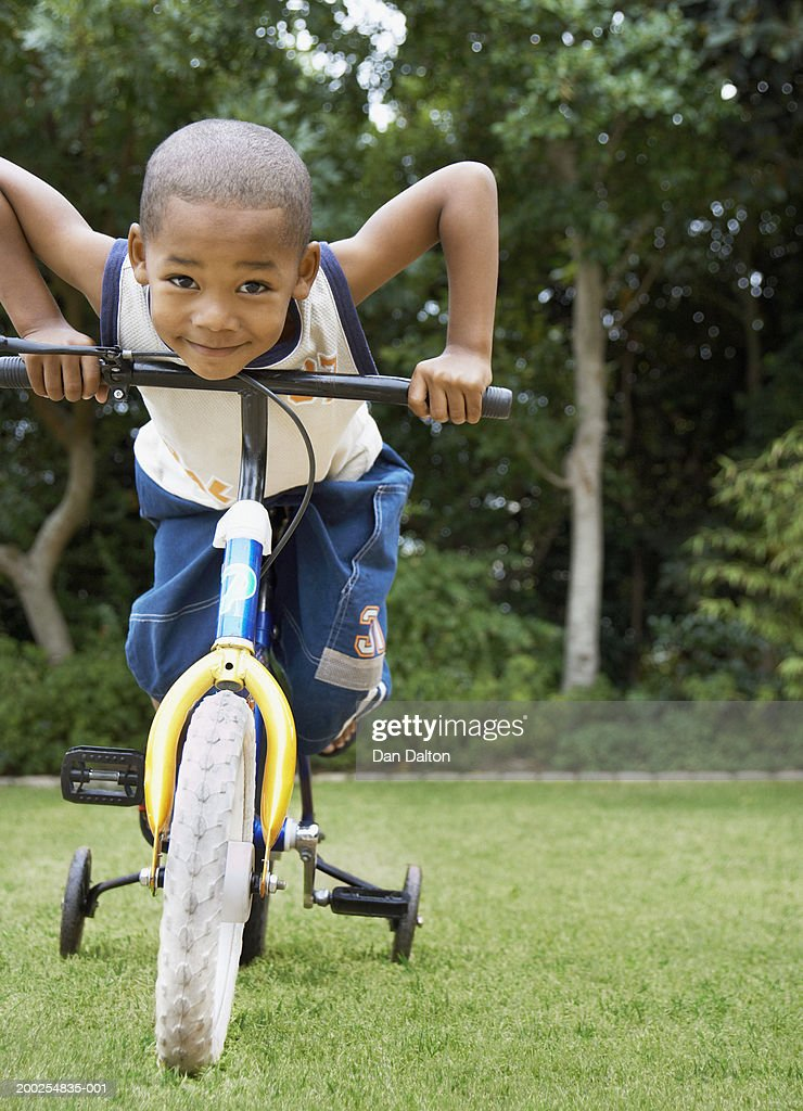 Boy (4-6) riding bicycle with stabilisers in garden, smiling, portrait : Stock Photo