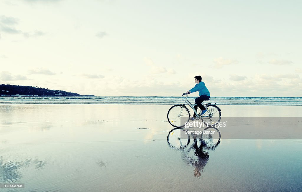 Boy riding bike at beach : ストックフォト