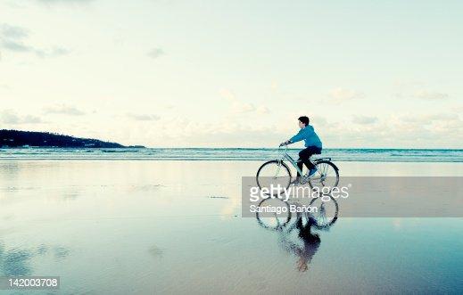 Boy riding bike at beach : Photo