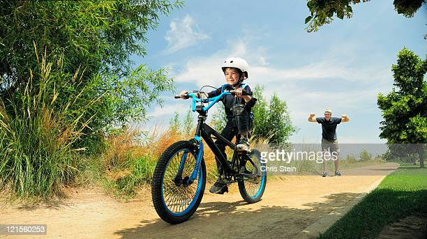 Boy riding bike by himself cheered on by father.