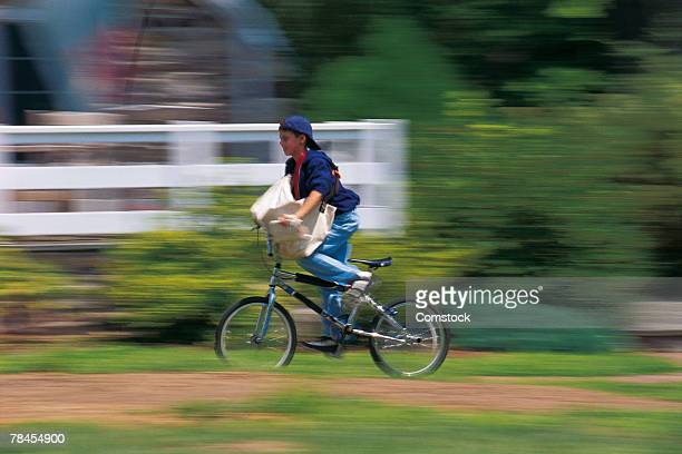 Boy riding his bike on paper route