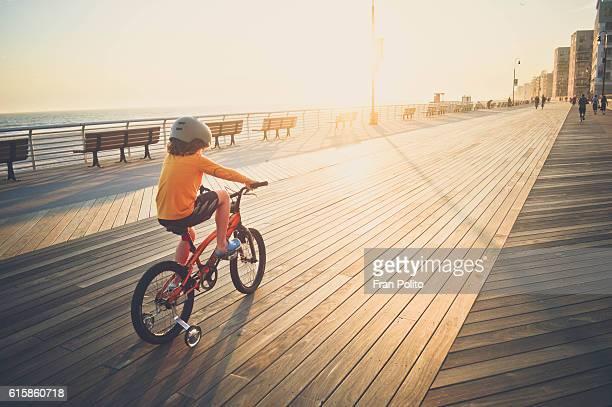 Boy riding his bike on the boardwalk.