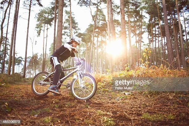Boy riding his BMX through forest