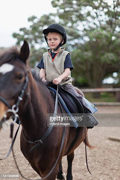 Boy riding horse in yard