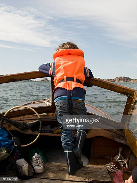 A boy riding in a motorboat, rear view
