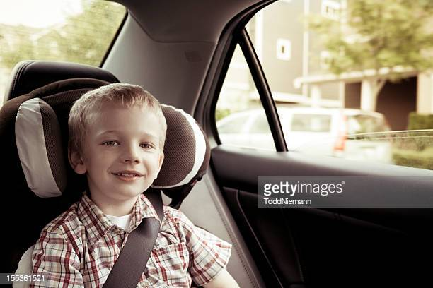 Boy riding in car with a smile