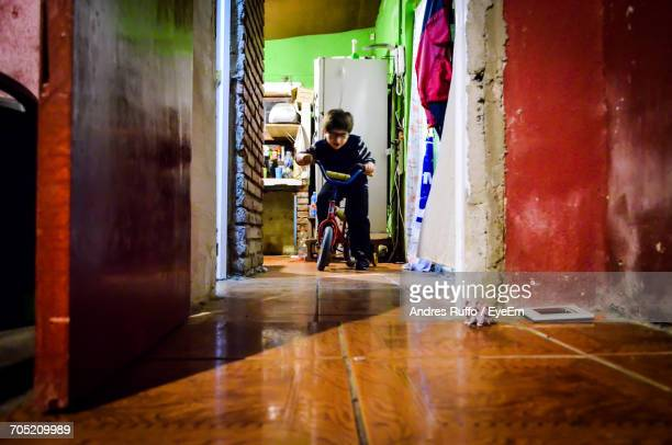 Boy Riding On Bicycle In Corridor At Home