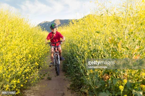 Boy Riding Through Yellow Flowers