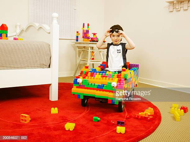 Boy (4-6) riding toy car made of blocks