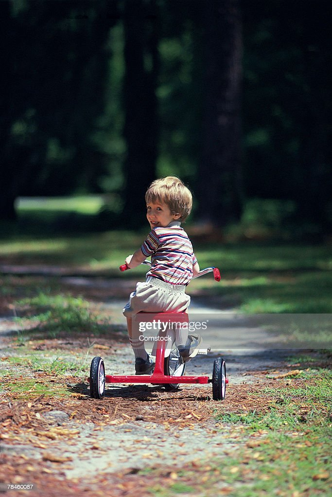 Boy riding tricycle in park