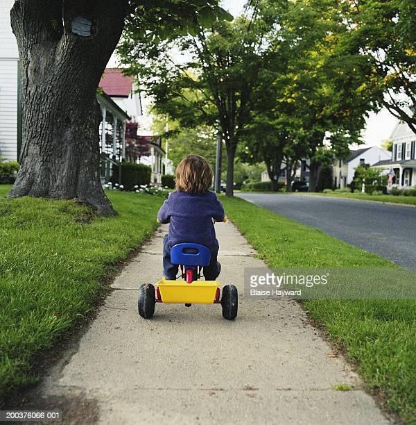 Boy (3-5) riding tricycle on sidewalk, rear view