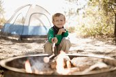 Boy roasting marshmallow over campfire