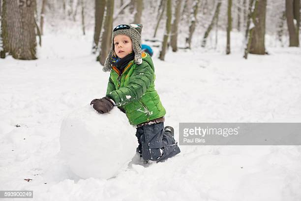 Boy (4-6) rolling large snowball on ground