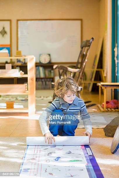 Boy rolling up poster in classroom