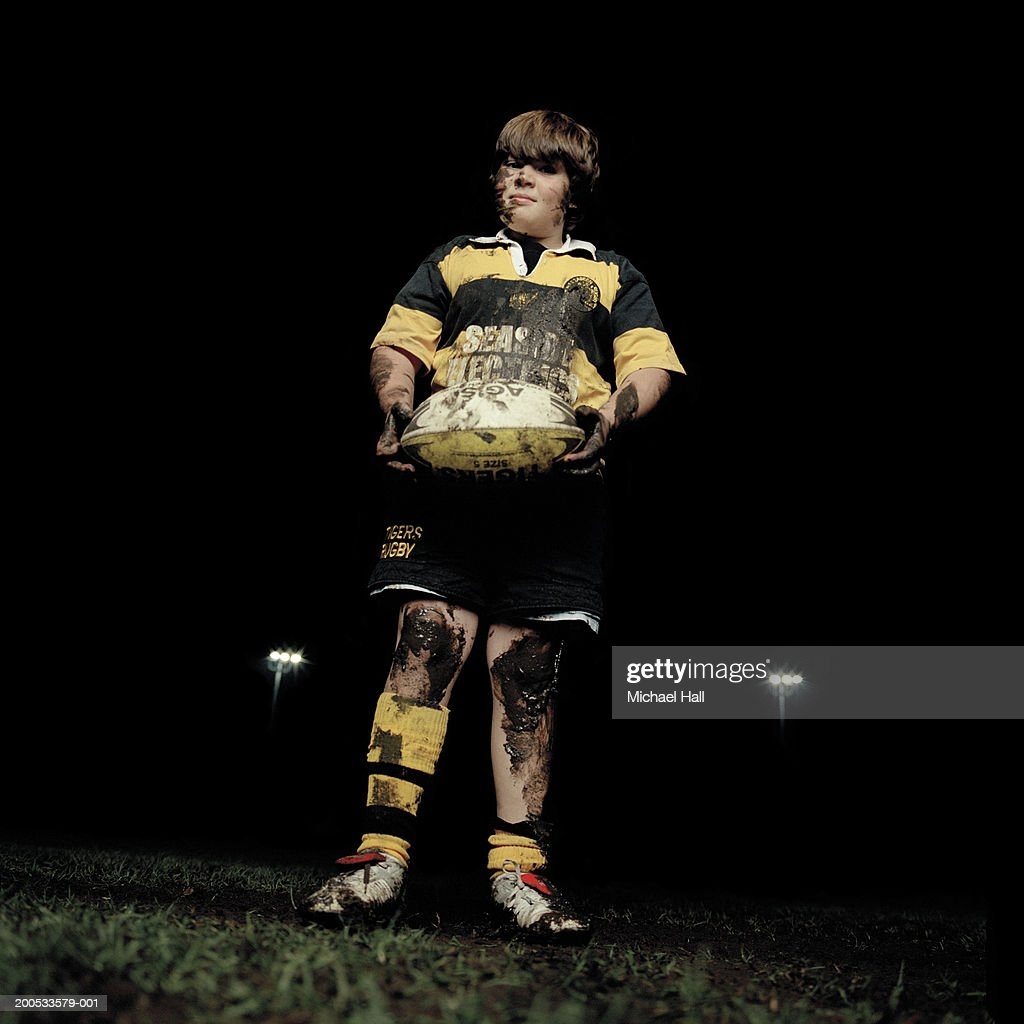 Boy (11-13) rugby player holding ball on pitch, portrait, night : Stock Photo