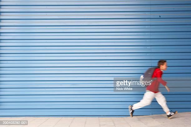 Boy (8-10) running along wearing rucksack, side view (blurred motion)