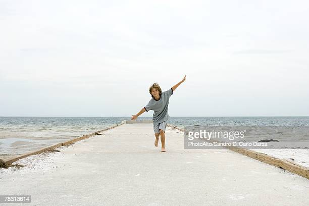 Boy running at the beach with arms outstretched, front view