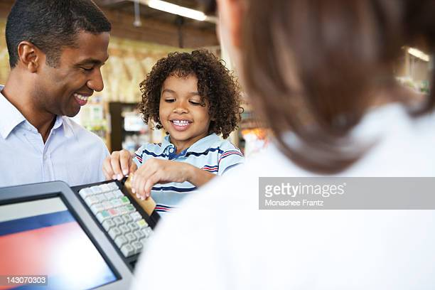 Boy running father's credit card at supermarket