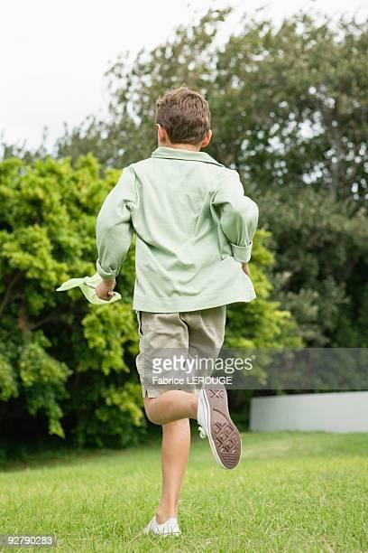 Boy running in a garden with a butterfly net