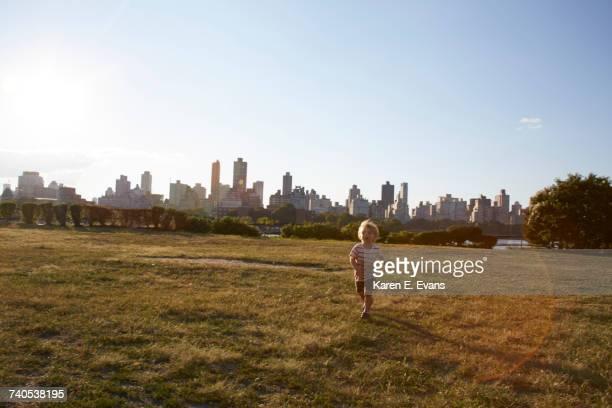 Boy running in park in front of New York skyline, USA