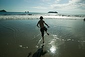 Boy (10-11) running in sea