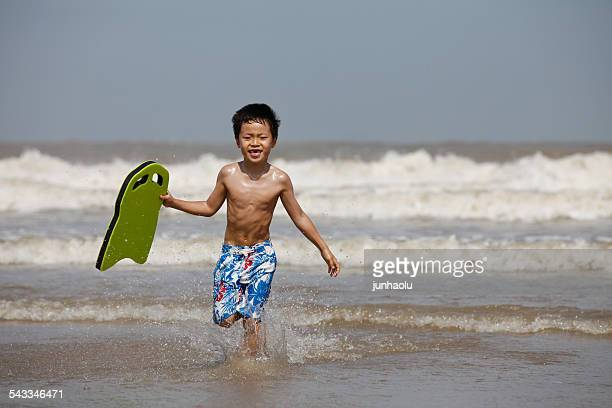 Boy (6-7) running in sea