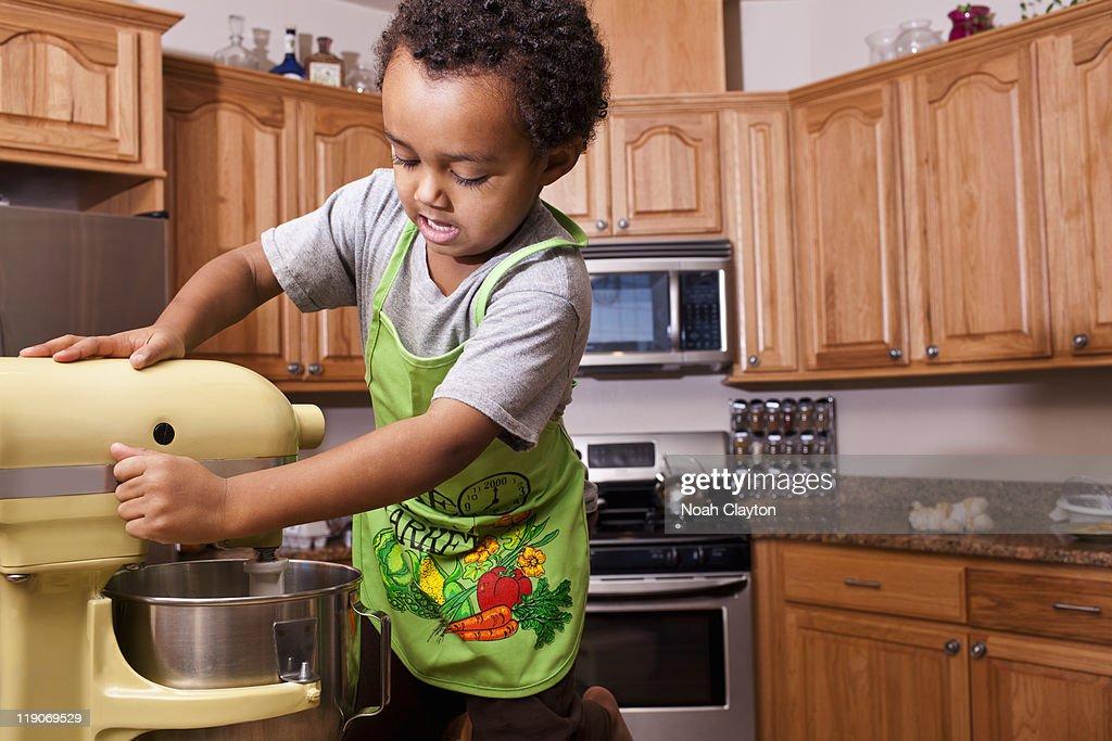Boy running mixer in kitchen