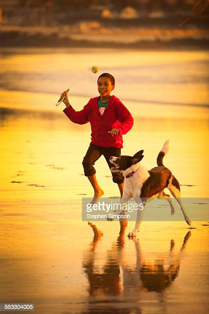 boy running on beach at low tide with dog