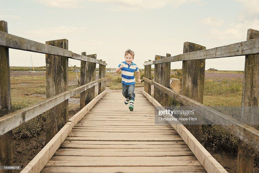 Boy running on footbridge : Stock Photo