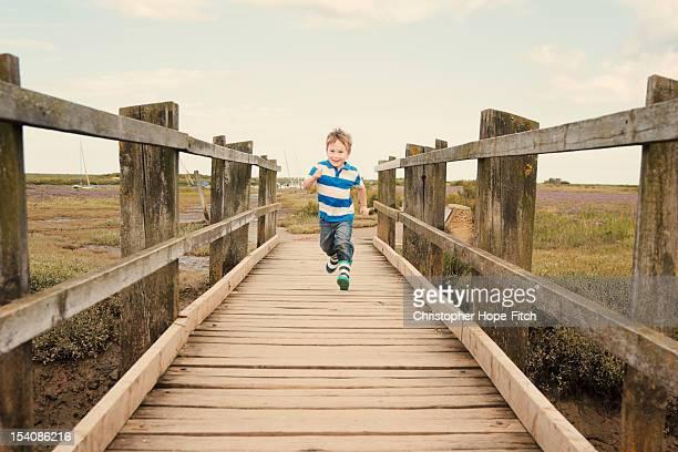Boy running on footbridge