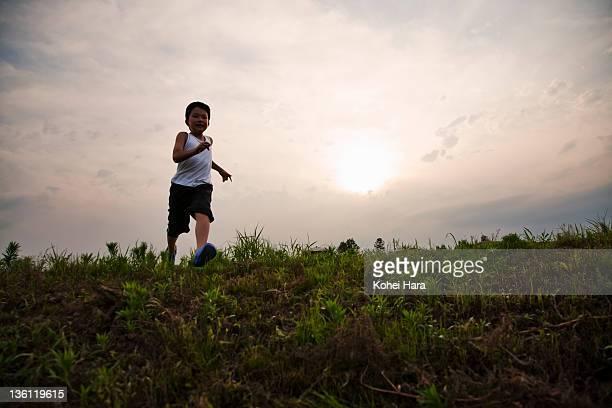 boy running on grass field at dusk