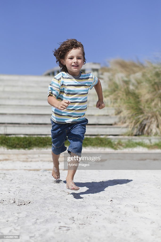 Boy running on sandy beach : Stock Photo