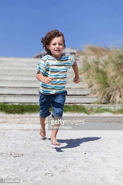 Boy running on sandy beach