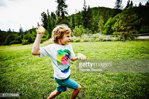 Boy running through field throwing water balloon