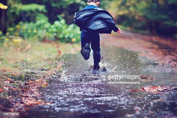 boy running through mud puddle